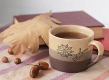 Autumn tea. A cup of tea with autumn leaves, acorns and books Stock Photo