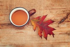 Autumn tea in brown vintage cup on old rustic wooden table, with autumn leave. royalty free stock photos
