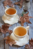 Autumn tea. Green tea in vintage mugs on wooden table with dry fall leaves. Selective focus Royalty Free Stock Images