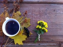 Autumn tea mug. Mug of tea, autumn leaves and yellow flowers on a old brown wood background Stock Photos