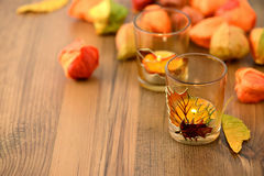 Autumn tealight decoration on table with chinse lantern seeds Royalty Free Stock Photos