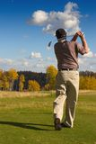 Autumn Tee Off. A man tees off on a golf course in autumn stock photography
