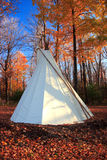 Autumn teepee. A traditional North-American Indian tepee in autumn in a forest in Quebec, Canada. Colorful trees, dead leaves and deep blue sky can be seen stock images