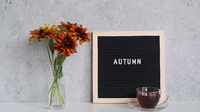 Autumn text on black letter board, bouquet of orange flowers in vase and cup of tea on table against grey stone wall. Template for postcard, greeting card stock video