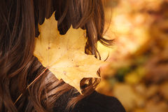 Autumn theme. Big yellow maple leaf in female hair Royalty Free Stock Photo