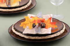 Autumn theme place setting. With brown plates and colorful fabric leaves on pale green background Royalty Free Stock Images