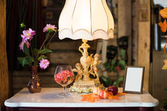 Autumn theme still life. A still life with autumn leaves and family photo on a table with a lamp stock image
