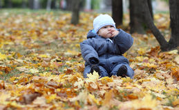 Autumn thoughts. A thoughtful child sitting on the ground in autumn park Stock Photos