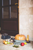 Autumn on threshold. Pumpkin and vegetables in front of door Royalty Free Stock Image