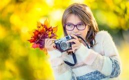 Autumn Time La chica joven linda atractiva adolescente con el ramo del otoño y la cámara retra Estación del otoño del fotógrafo d Foto de archivo libre de regalías