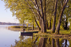 Autumn time lake landscape with boat and tree Royalty Free Stock Photos