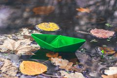 Autumn time. Paper boat and fallen dry leaves on the water surface. Beautiful nature background. Goodbye autumn. Autumn time. Paper boat and fallen dry leaves royalty free stock image