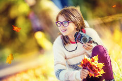 Autumn time. The teenage attractive cute young girl with autumn bouquet and retro camera. Young girl photographer autumn  season.  Stock Images