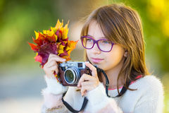 Autumn time. The teenage attractive cute young girl with autumn bouquet and retro camera. Young girl photographer autumn  season.  Stock Photo