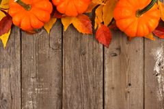 Autumn top border of pumpkins and leaves against rustic wood. Autumn top border of pumpkins and leaves against a rustic old wood background Stock Photo
