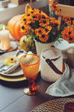 Autumn traditional seasonal table setting at home with pumpkins, candles and flowers. Celebrating Thanksgiving Royalty Free Stock Photos