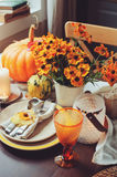 Autumn traditional seasonal table setting at home with pumpkins, candles and flowers. Celebrating Thanksgiving Royalty Free Stock Images