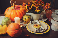 Autumn traditional seasonal table setting at home with pumpkins, candles and flowers. Celebrating Thanksgiving stock images