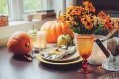 Autumn traditional seasonal table setting at home with pumpkins, candles and flowers Royalty Free Stock Image
