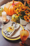 Autumn traditional seasonal table setting at home with pumpkins, candles and flowers Stock Image