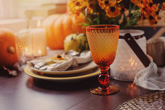 Autumn traditional seasonal table setting at home with pumpkins, candles and flowers. Family celebrating Thanksgiving day royalty free stock images