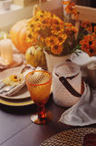 Autumn traditional seasonal table setting at home with pumpkins, candles and flowers. Family celebrating Thanksgiving day Royalty Free Stock Photos