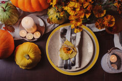 Autumn traditional seasonal table setting at home with pumpkins, candles and flowers. Family celebrating Thanksgiving day Stock Images