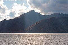 Autumn tree on mountain and lake with sunray.  stock image