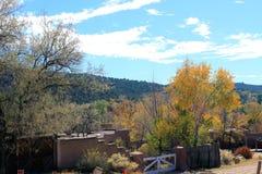 Autumn Trees et bâtiments au pied de la montagne Photo stock