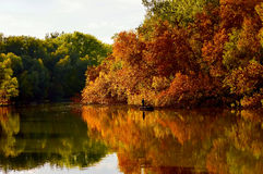 Autumn trees and lake and anglers Royalty Free Stock Image