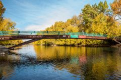 Autumn trees line the Boise River with a foot bridge with signs. Boise River with autumn color reflections beneath a foot bridge royalty free stock photography