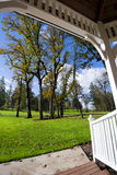 Autumn trees in meadow with grass from wooden gazebo Stock Photo