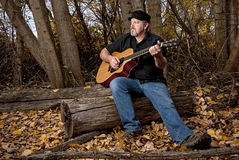 Autumn trees and a professional guitarist Royalty Free Stock Photo