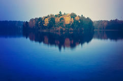 Autumn trees reflecting on lake. Scenic view of autumn trees reflecting on blue water of lake at night stock photography