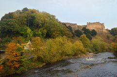 Autumn trees by the river swale and richmond castle. Autumn trees by the river swale near to Richmond Yorkshire on the edge of the Yorkshire Dales National Park royalty free stock photography