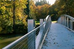 Aurum trees across bridge. Autumn trees surrounding park across shiny steel bridge over river Royalty Free Stock Photography