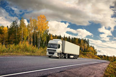 Autumn truck highway. White truck on autumn highway Royalty Free Stock Photo