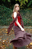 Autumn twirl. Young woman in autumn twirling her skirt royalty free stock photography