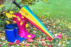 Autumn. Two pairs of rubber boots and colorful umbrella with autumnal leaves. Pairs of pink (adult) and blue (child) rainboots. Protection in the rain. Copy Stock Photos