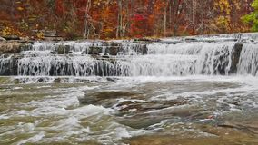 Autumn at Upper Cataract Falls Loop. Whitewater flows over limestone ledges backed by vibrant, colorful fall foliage at Upper Cataract Falls, a waterfall in stock video