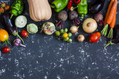 Autumn vegetable harvest. Pumpkin, eggplant, peppers, carrots, tomatoes, onions, garlic, beets on a dark background, top view. Stock Photography