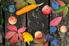 Autumn vegetables and fruits on an old wooden background outdoors. royalty free stock photography