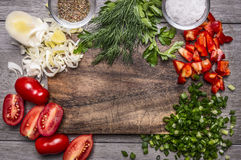 Autumn vegetables and herbs on a cutting board with spices and salt on wooden background close up top view space for text Royalty Free Stock Photo