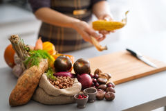Autumn vegetables in a kitchen with anonymous woman husking corn Royalty Free Stock Photography