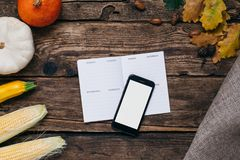 Autumn vegetables: mobile phone with white empty screen, pumpkins and corn with yellow leaves on a wooden background. Top vector illustration