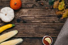 Autumn vegetables:tea, pumpkins and corn with yellow leaves on a wooden background stock image