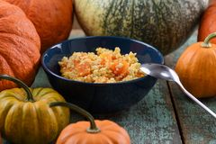 Autumn vegetarian meal. Millet and pumpkin porridge in navy blue. Bowl served with raw organic pumpkins on rustic blue background closeup royalty free stock images