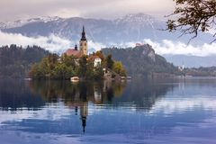 Autumn view of  the historical church on the island in Lake Bled. In front of snow capped mountains under clouds Stock Image