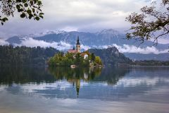 Autumn view of  the historical church on the island in Lake Bled before snow capped Alps. Under clouds Royalty Free Stock Photo