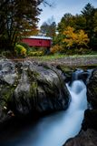 Northfield Falls & Slaughterhouse Covered Bridge - Long Exposure Waterfalls - Vermont. An autumn view of Northfield Falls and Slaughterhouse Covered Bridge in royalty free stock photography